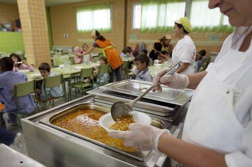 cuineres servint menjar en un menjador escolar