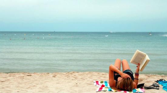 noia llegint a la platja